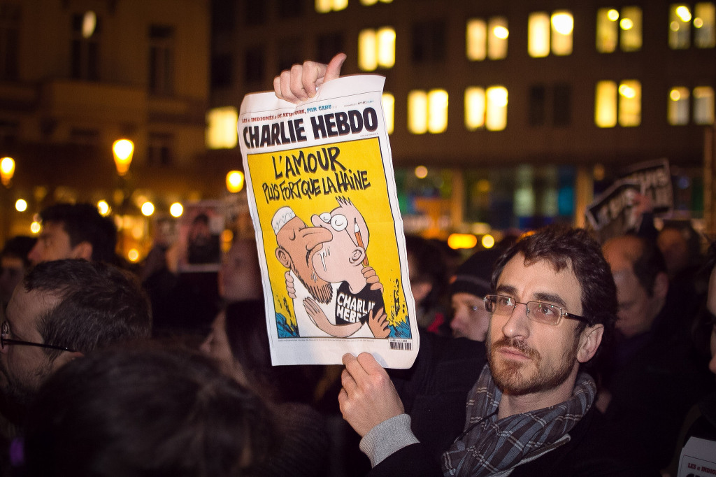 A supporter of Charlie Hebdo holds up a copy of the magazine Wednesday at a rally in Brussels.