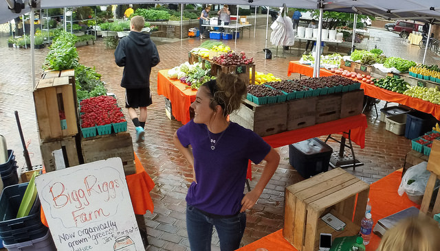 Shaylyn Bohrer looks out across the Old Town Market Square, ready for Bigg Riggs Farm customers, at the historic Old Town Farmers' Market, in Alexandria, Va.
