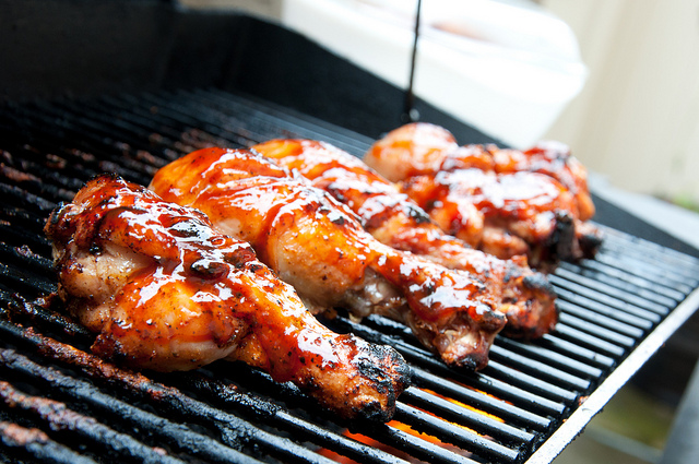 Barbecue chicken drumsticks on a grill.