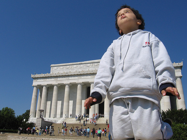 A child stands in front of the Lincoln Memorial and looks towards the direction of the Washington Monument and U.S. Capitol.