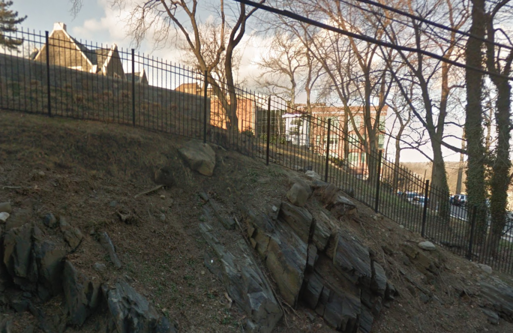 Part of Horace Mann School in the Bronx, obscured by rock.