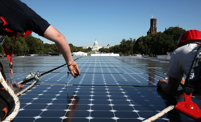Students Lutz Steiner, left, and Henning Zimmer of Team Germany, set the last solar panel on their team's house during the 2009 U.S. Department of Energy Solar Decathlon on the National Mall in Washington, D.C.