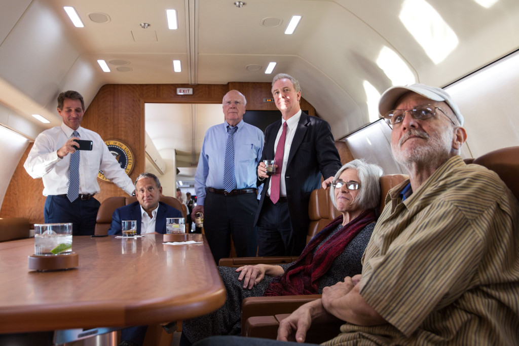Alan Gross with his wife Judy, attorney Scott Gilbert, Rep. Chris Van Hollen, D-Md., Sen. Patrick Leahy, D-Vt., and Sen. Jeff Flake, R-Ariz. watch television onboard a government plane headed back to the US as the news breaks of his release, Dec. 17, 2014.