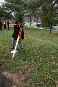 A student in the Design Apprenticeship Program surveys land.