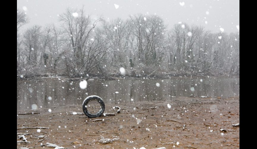 A tire on the Anacostia River in winter.