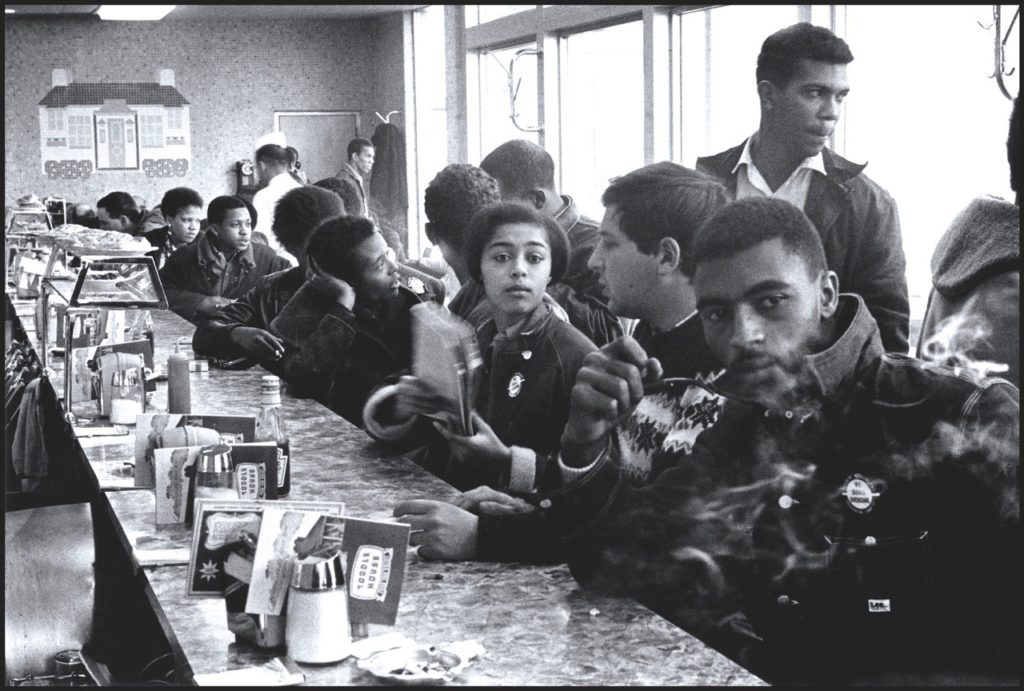 Judy Richardson (center) with other SNCC staff workers, including Joyce Ladner (to left of Richardson, talking to John Lewis, whose head is shown behind Ladner), during a sit-in at the Toddle House restaurant, shortly before their arrest  (Atlanta, December 1963).