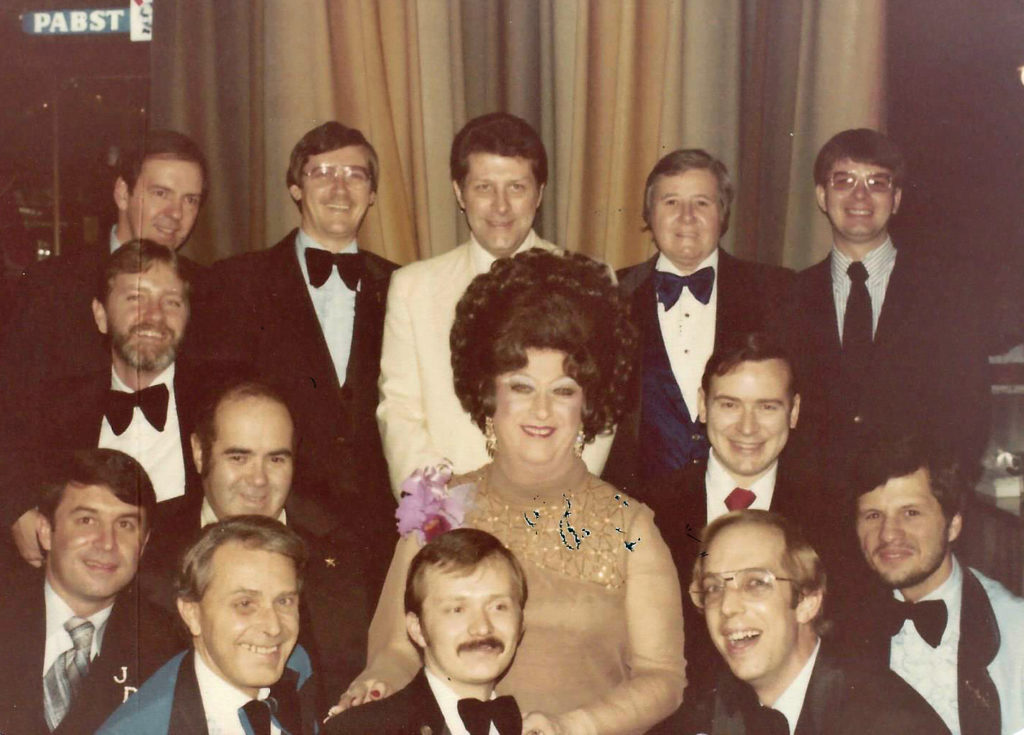 "Carl Rizzi performed in drag as Mame Dennis (center). Rizzi led The Academy of Washington, a drag organization, from 1973 until his death in 2015. Above, Rizzi sits with his ""nephews."""