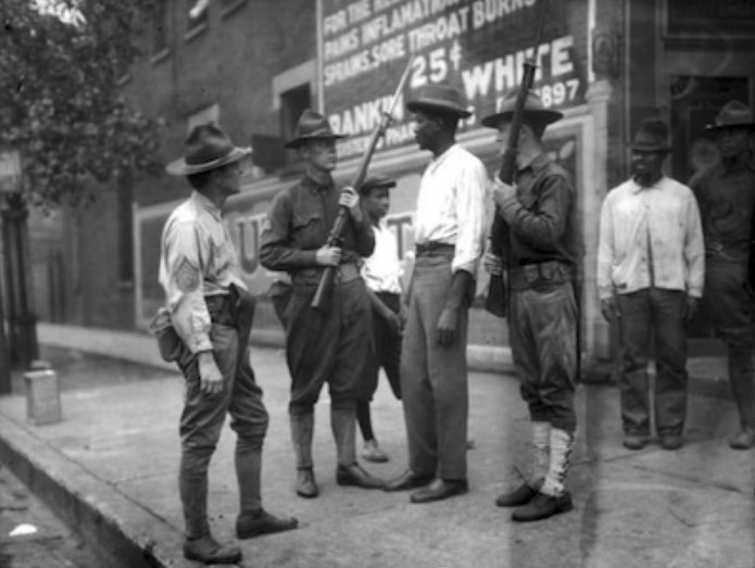 Three armed soldiers question an unidentified African American man in D.C. during the 1919 race riots.