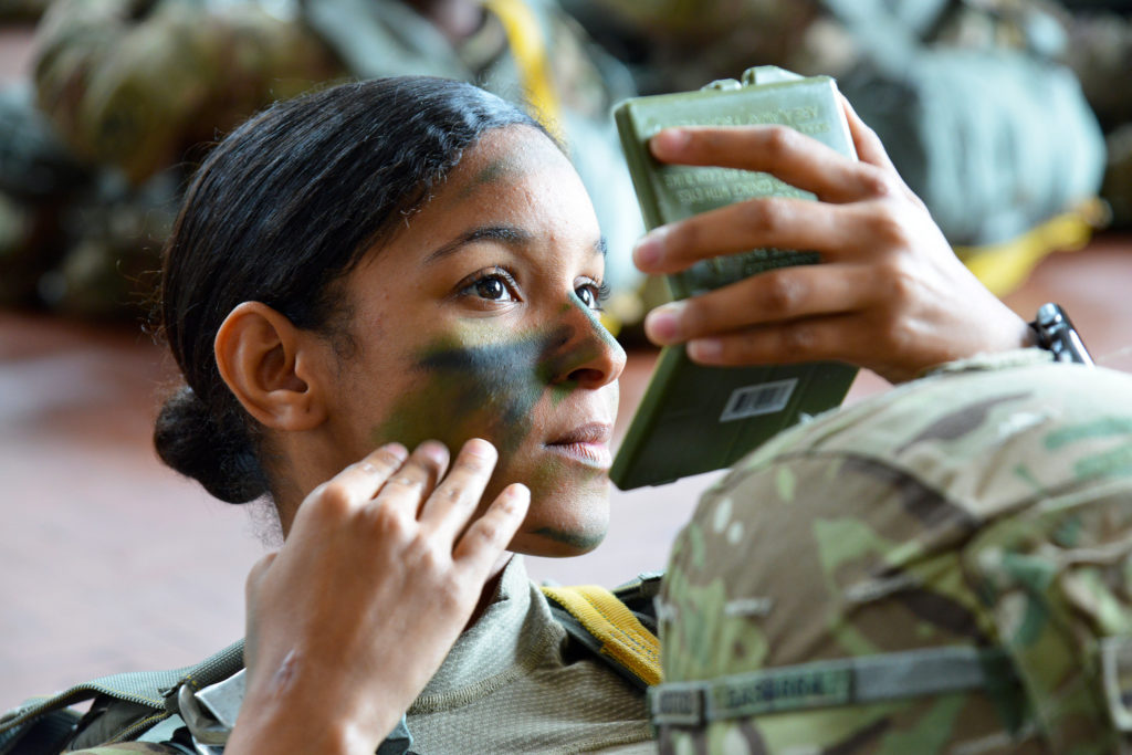 U.S. Army Paratrooper assigned to the 54th Brigade Engineer Battalion, 173rd Airborne Brigade, puts the finishing touches to her face paint camouflage at Villafranca Air Base