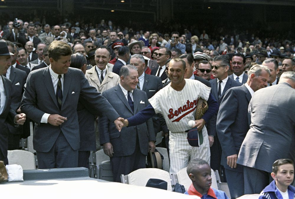 President John F. Kennedy laughs as Washington Senators catcher, Ken Retzer, grasps his hand during opening day of the 1963 baseball season at D.C. Stadium, Washington, D.C.; the Washington Senators hosted the Baltimore Orioles.