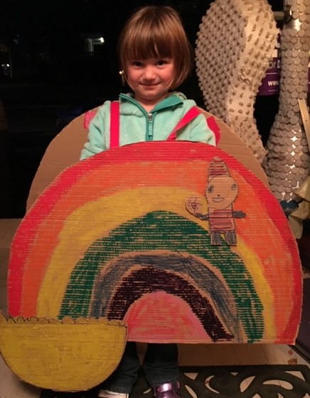 Kit Smallwood dressed as a rainbow with a leprechaun named Roy G. Biv.