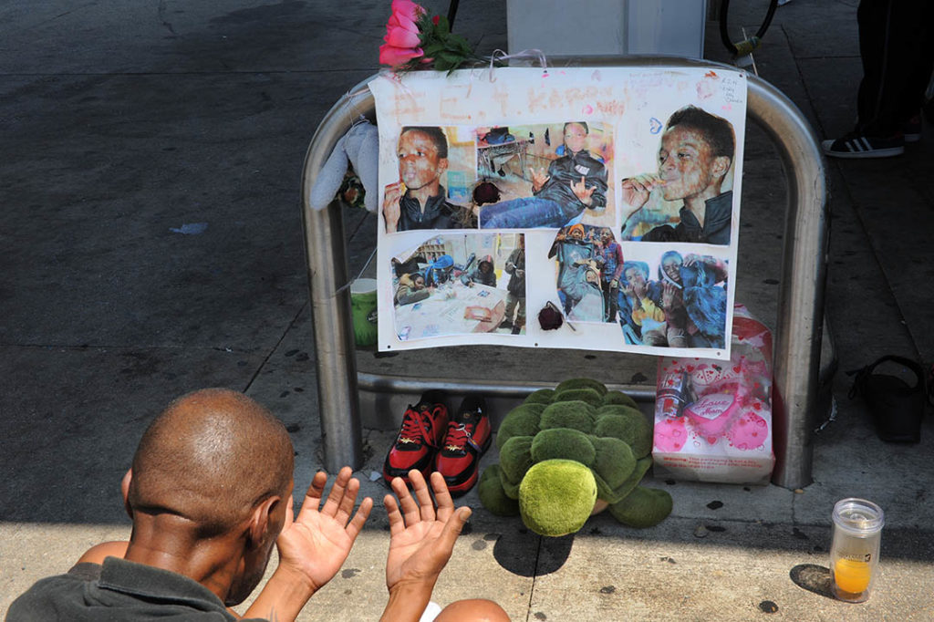 Karon Brown, 11, was killed in July. The man pictured is his grandfather, praying  and watching vigil over his memorial.