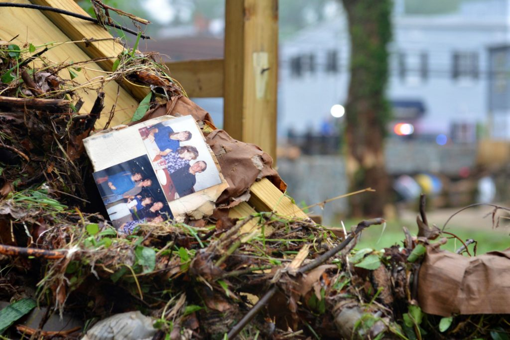 "Family photos rest among debris after flash flooding in Ellicott City, Maryland in May 2018. The ""thousand year storm"" was the second destructive flood to hit the mill town in less than two years."