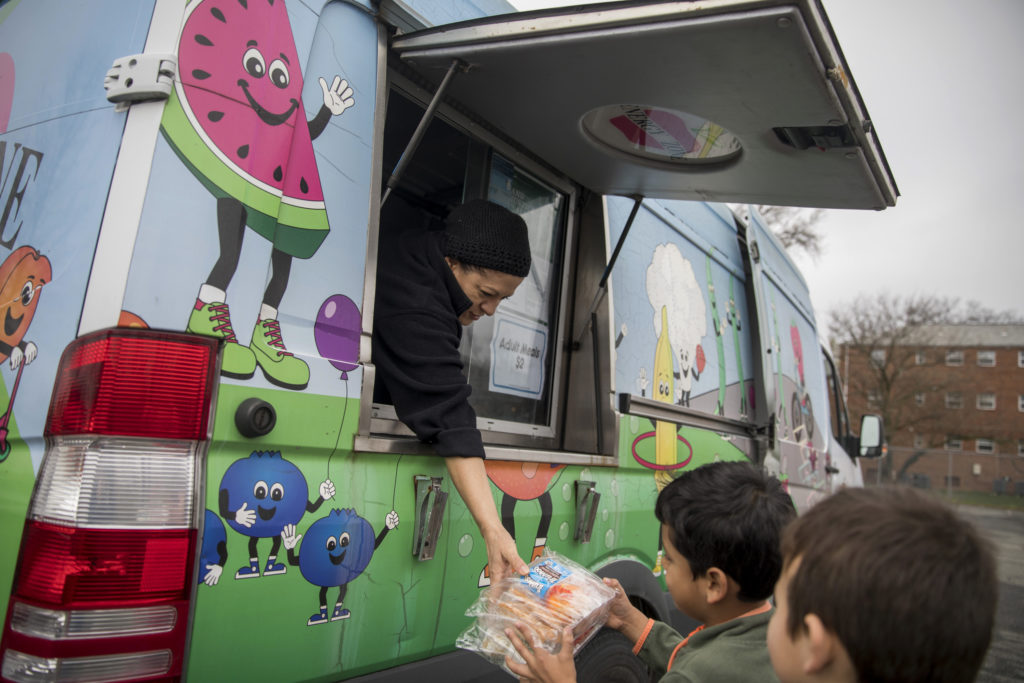 """In Falls Church, Virginia, Fairfax County Food and Nutrition Services food truck set up """"pop-up"""" distribution sites of free meals for children under 18."""