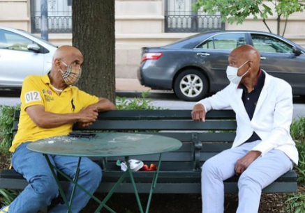 Two men in masks chat on a bench on North Charles Street in Baltimore on Saturday evening, May 23, 2020.