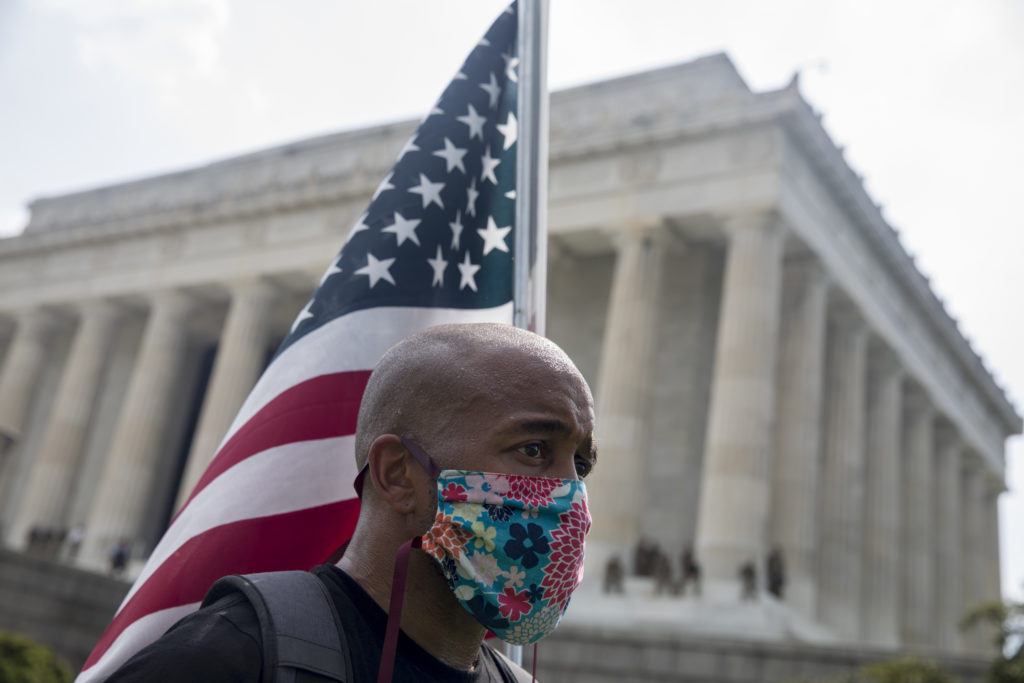 A protester carrying an American flag stands near the Lincoln Memorial on June 6, 2020.