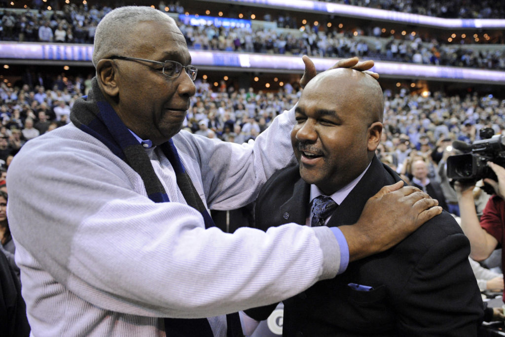 Former Georgetown coach John Thompson Jr., left, congratulates his son John Thompson III, right, after the Hoya's 61-39 win over Syracuse in an NCAA college basketball game  in 2013.