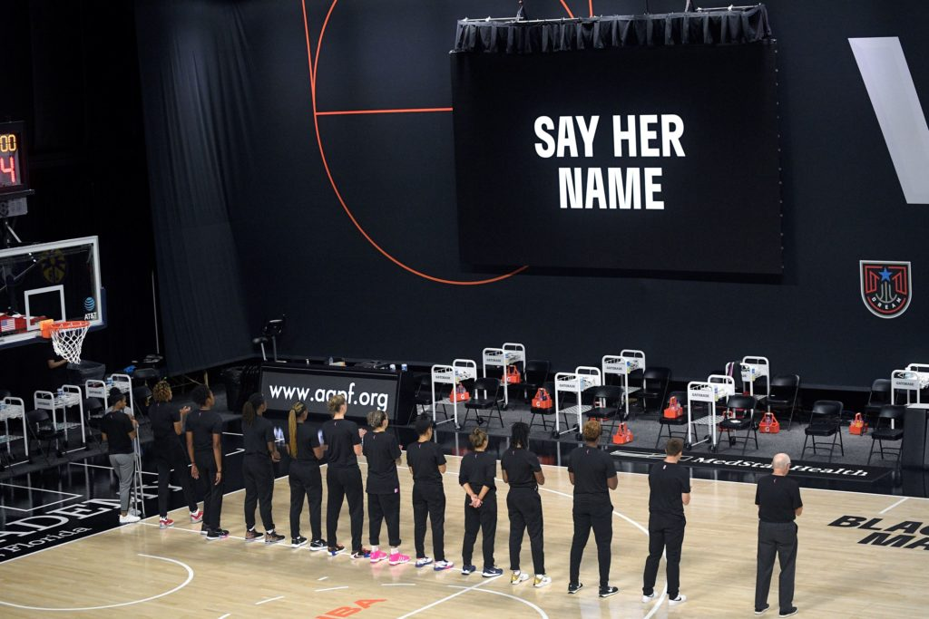 Members of the Washington Mystics team stand in silence before a WNBA basketball game against the Connecticut Sun in August.
