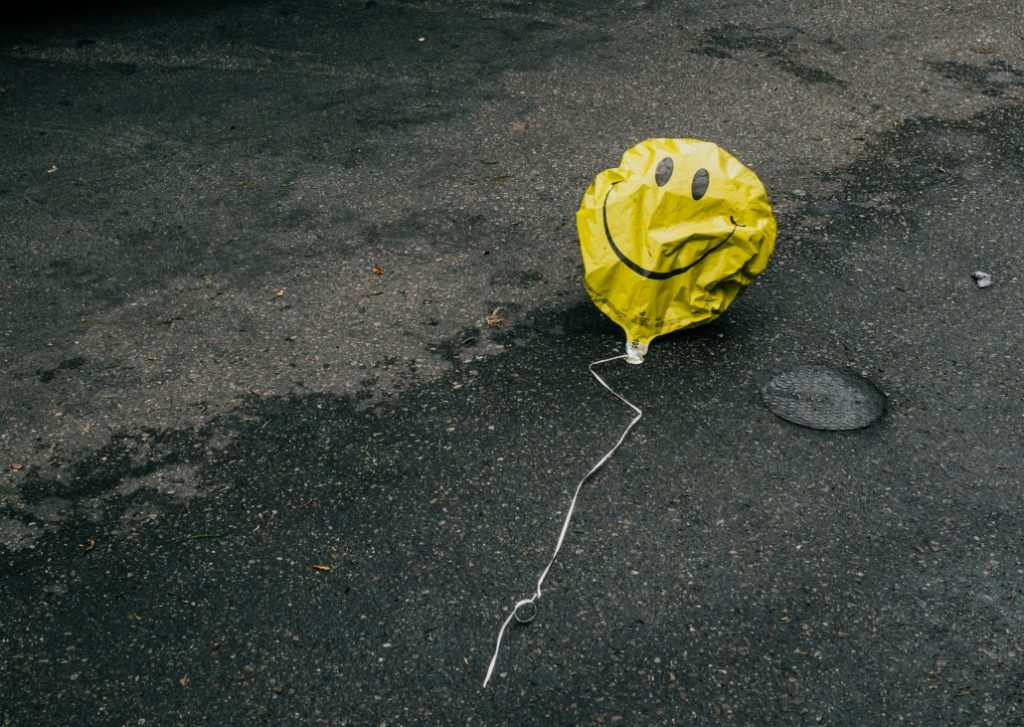 Partially deflated happy face balloon.