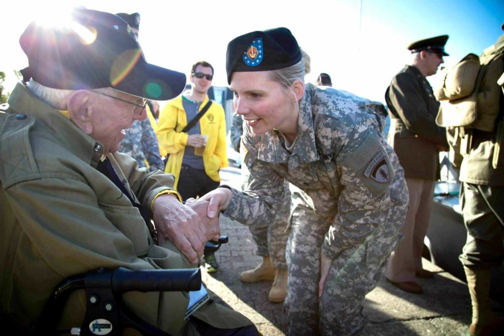 Victoria Chamberlin shakes the hand of a World War II paratrooper on June 6th, 2014 at a D-Day commemoration in Normandy, France.