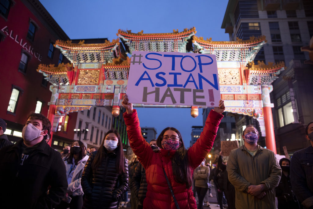 Kira Hung, of Alexandria, Virginia, holds a sign during the demonstration in Chinatown.
