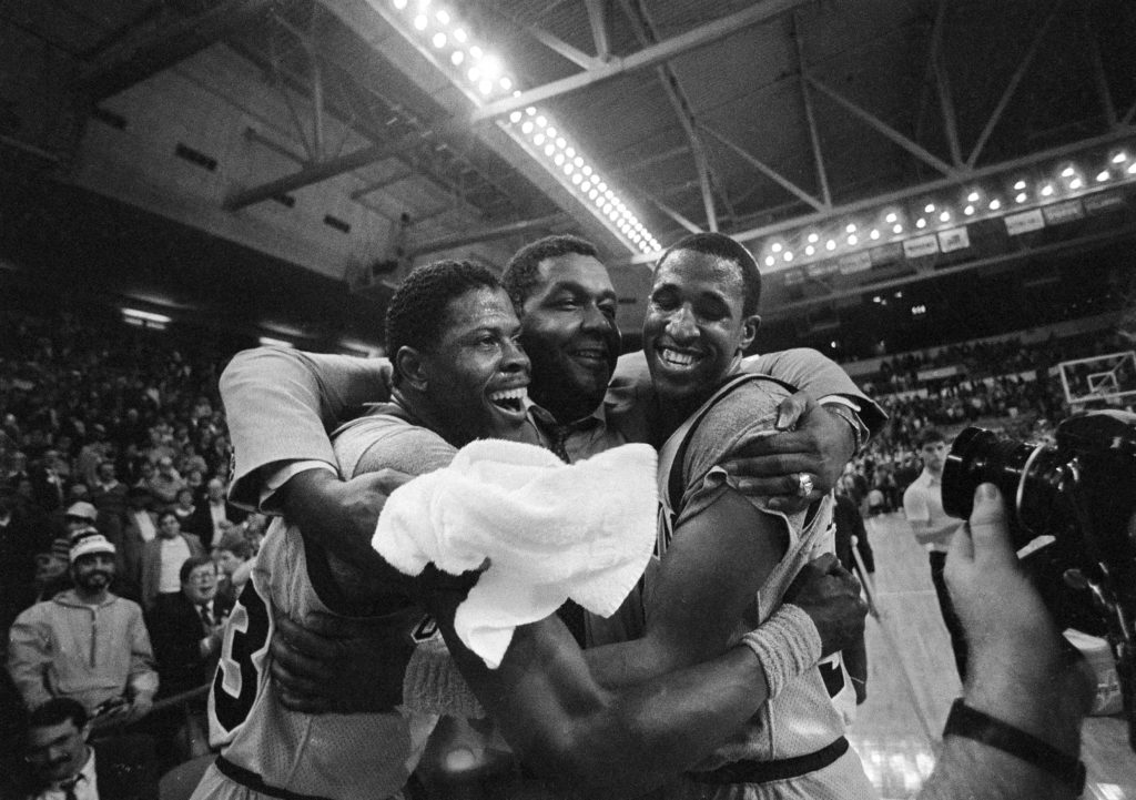 Georgetown University's Patrick Ewing, left, and teammate Ralph Dalton, right, get a hug from head coach John Thompson, center, after Georgetown beat Georgia Tech 60-54 during NCAA action at the Providence, R.I. Civic Center, March 24, 1985.
